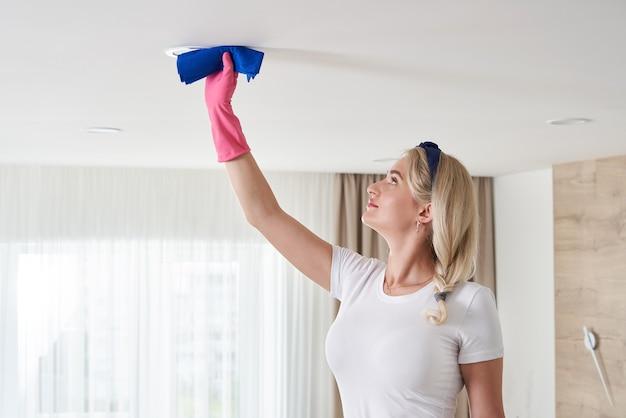 Femme de chambre tenant la pile de vadrouille, nettoyage du plafond dans le salon. concept de service de nettoyage de maison.