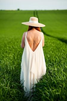 Femme sur le champ vert en robe blanche