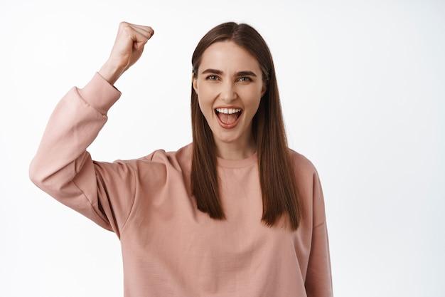 Femme chantant, enracinant pour l'équipe. une militante levant son poing pour lutter contre l'égalité, la pompe à poing, a l'air encouragée et déterminée, debout sur du blanc.
