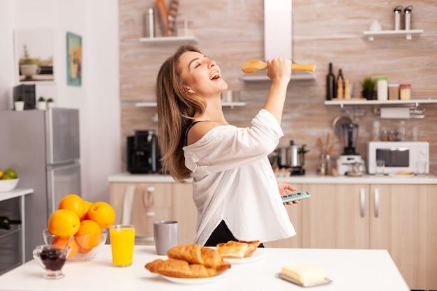 Femme chantant pendant le petit déjeuner dans la cuisine à domicile en lingerie sexy. femme séduisante avec des tatouages utilisant un smartphone portant des sous-vêtements temporaires le matin.