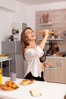 Femme chantant pendant le petit déjeuner dans la cuisine de la maison en lingerie sexy