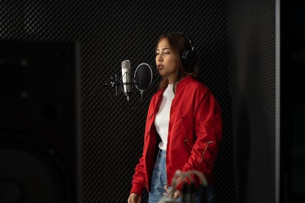 Femme chanteuse asiatique dans un studio d'enregistrement utilisant un microphone de studio avec passion dans un studio d'enregistrement musical