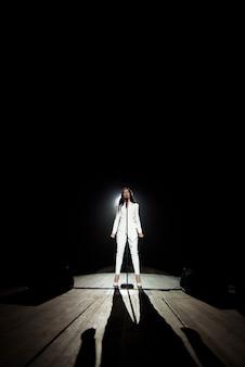 Femme chanteuse sur scène dans un faisceau de lumière blanche.