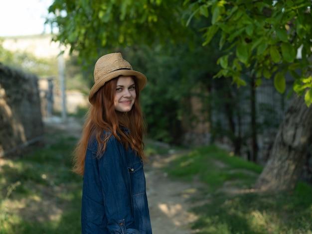 Femme avec chapeau à l'extérieur marche arbres reste
