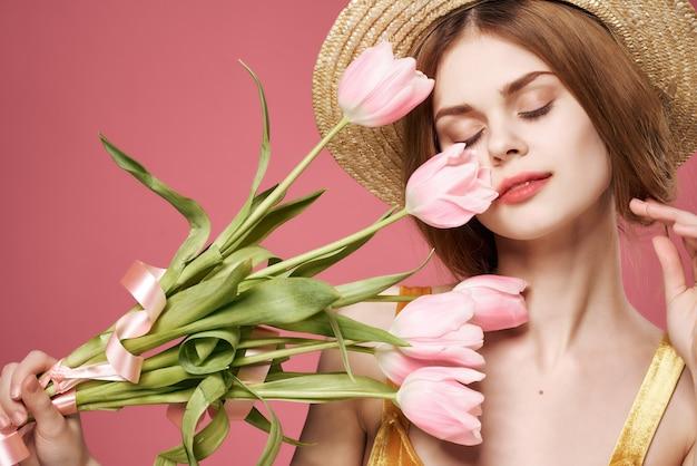 Femme avec chapeau fleurs fond rose charme intérieur