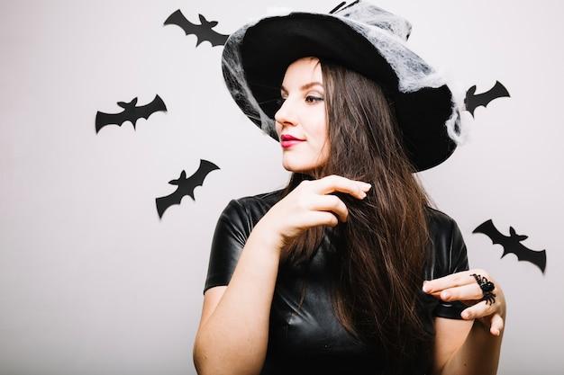 Femme en chapeau de halloween jouant avec des cheveux