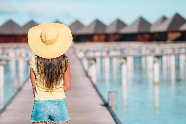 Femme avec un chapeau jaune se détendre à la piscine dans un complexe exotique