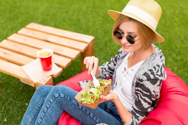 Femme, chapeau, manger, parc