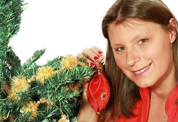 Femme avec chapeau de père noël décore un arbre de noël