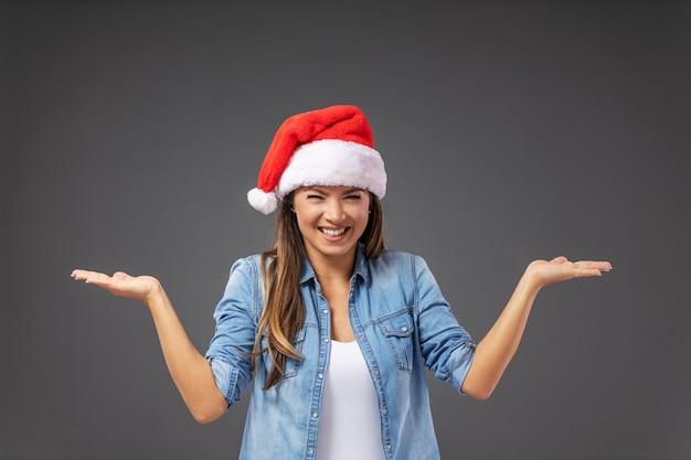 Femme avec chapeau de père noël habillé décontracté tenant les mains en l'air comme si elle tenait quelque chose.