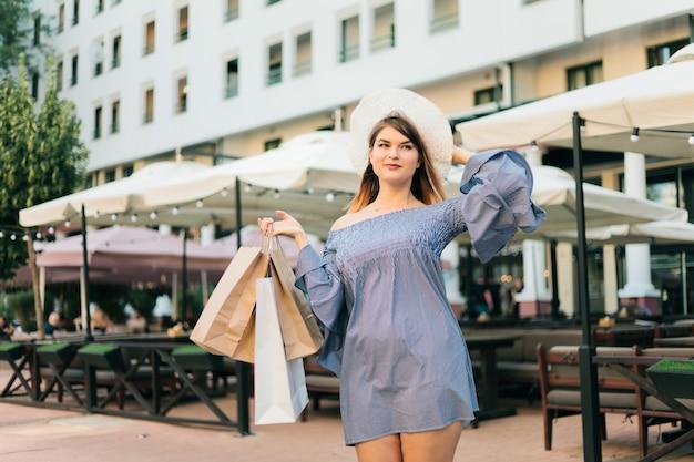 Femme, chapeau, robe, tient, sacs provisions, mains, sourires, été, ville