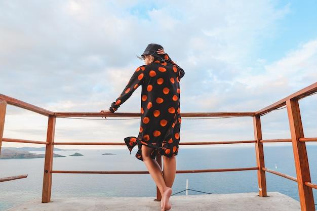 Une femme en chapeau de seau se tient au balcon et profite de la vue sur l'océan