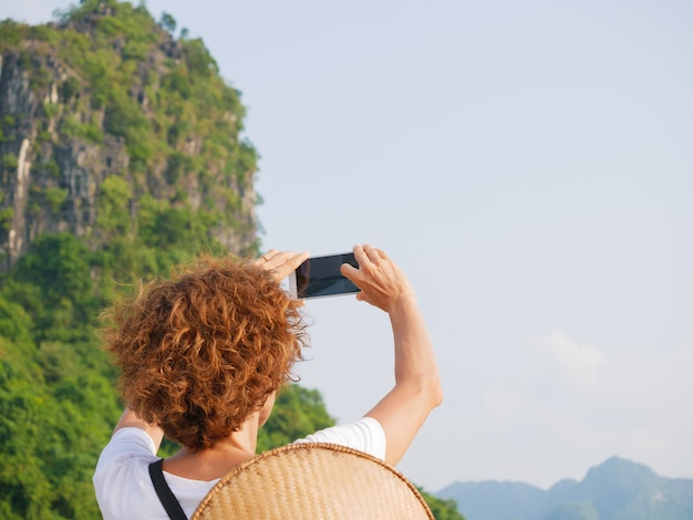 Femme avec chapeau traditionnel à l'aide de téléphone à la baie d'halong vietnam