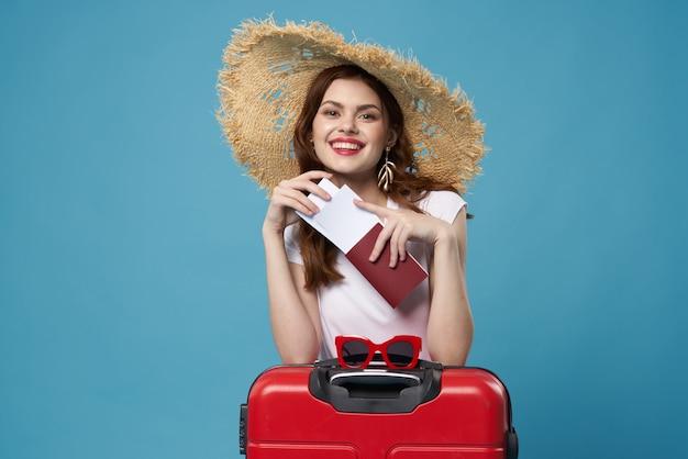 Femme avec chapeau valise rouge vacances vol aéroport fond bleu