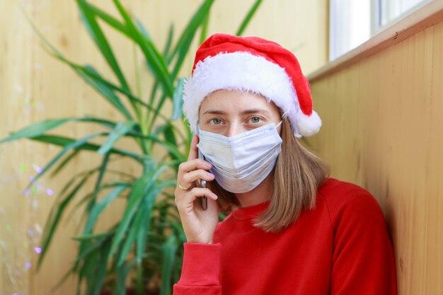 Une femme en chapeaux de père noël rouge et masque médical félicitant la famille ou les amis avec une tablette