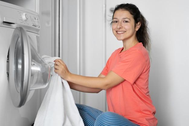 Une femme charge du linge sale dans une machine à laver alors qu'elle est assise par terre dans un appartement.
