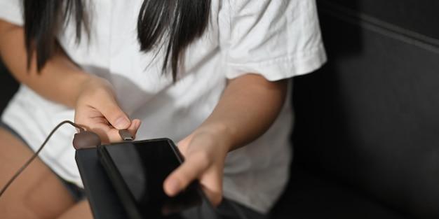 Une femme charge un smartphone assis sur le canapé en cuir noir
