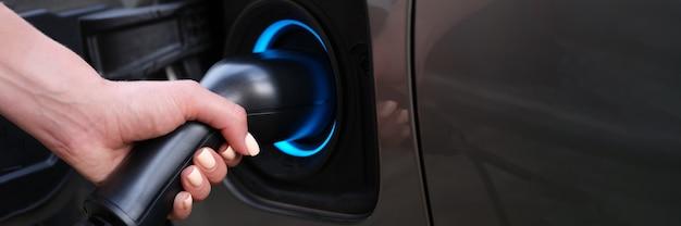 Femme chargeant une voiture à l'aide d'une prise électrique en gros plan
