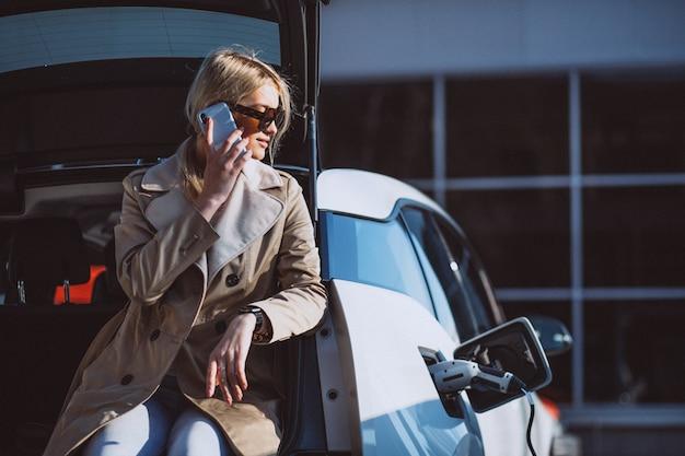 Femme chargeant une voiture électrique à la station d'essence électrique