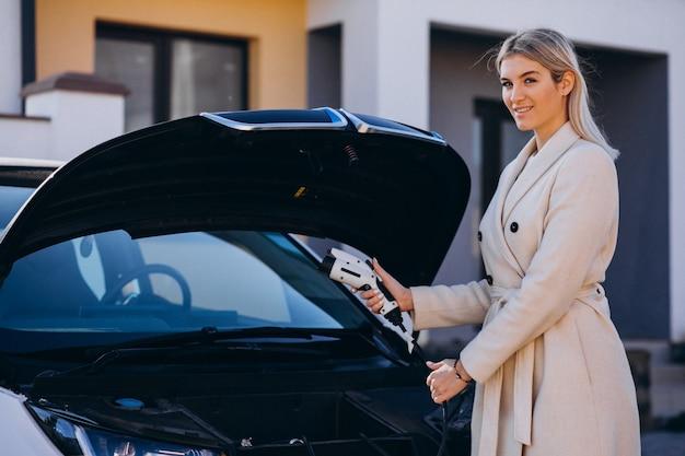 Femme chargeant une voiture electro devant sa maison et tenant un chargeur