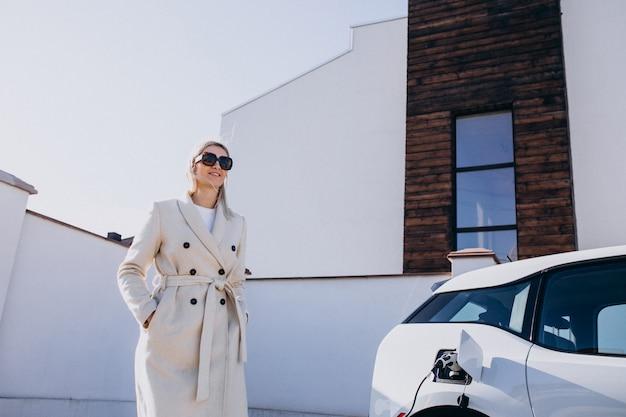Femme chargeant une voiture électro par sa maison