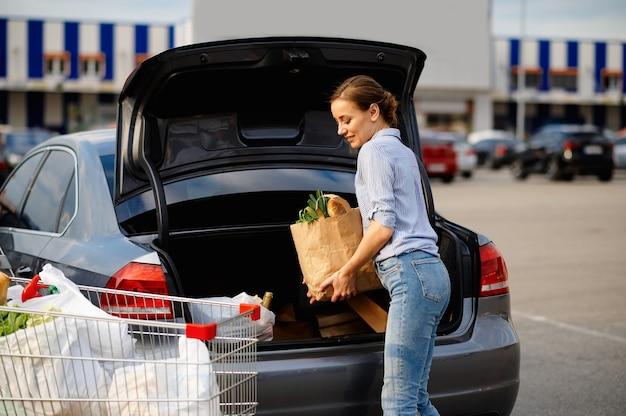 Femme avec chariot met ses achats dans le coffre de la voiture