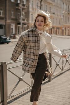 Femme charmante blonde bouclée dans un pantalon marron élégant, un chemisier blanc et un manteau à carreaux courant dans le centre-ville