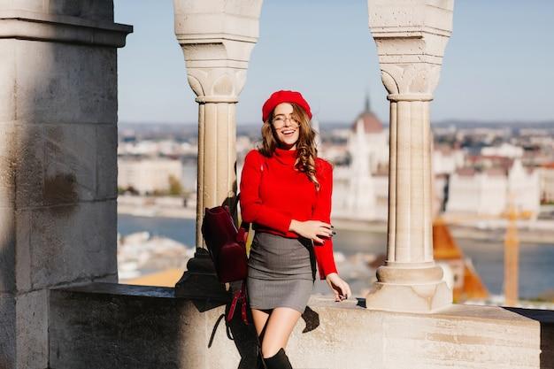 Femme charmante galbée en mini jupe posant avec un sourire heureux près de vieilles colonnes en pierre