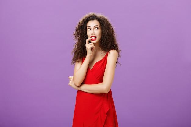 Femme charmante idiote et timide avec des cheveux bouclés noirs en robe de soirée élégante avec un doigt mordant de rouge à lèvres rouge qui a l'air mignon dans le coin supérieur droit une imagerie réfléchie ou rêvant d'une chose désirable.