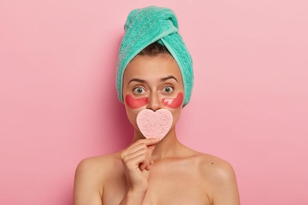 Une femme charmante a un maquillage minimal, applique des éponges cosmétiques sous les yeux, couvre la bouche d'une éponge en forme de cœur, a une peau parfaitement soignée, a l'air étonnamment, se tient à l'intérieur avec un corps nu