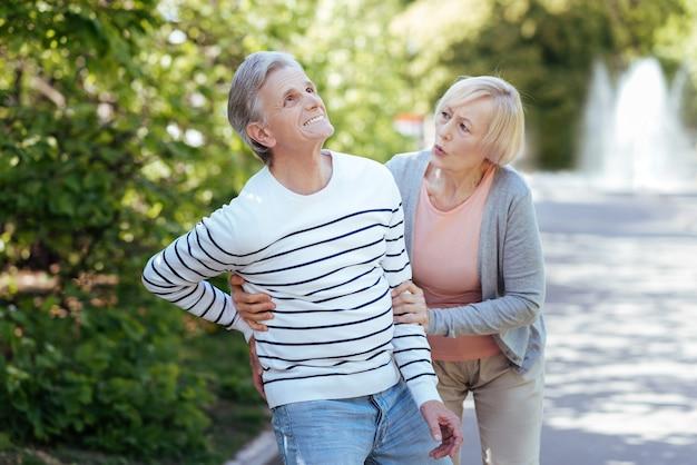 Femme charmante et qualifiée âgée se souciant de l'homme malade et le soutenant tout en marchant dans le parc
