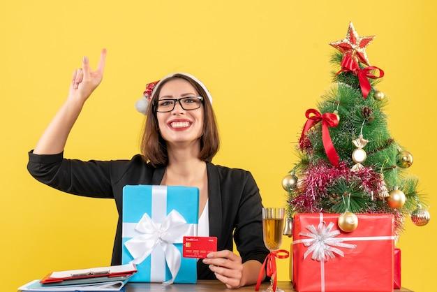 Femme charmante souriante en costume avec chapeau de père noël et lunettes montrant le cadeau et la carte bancaire pointant vers le haut dans le bureau sur jaune isolé