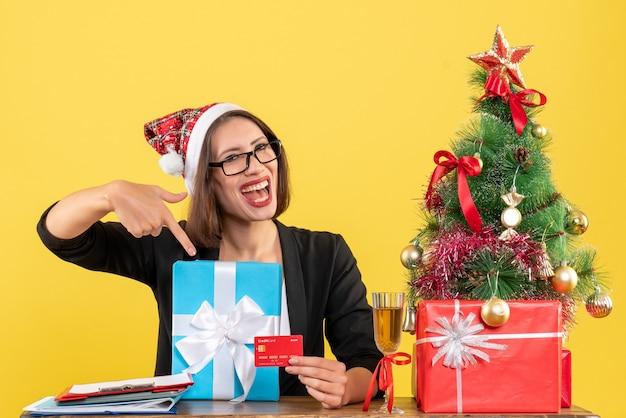 Femme charmante souriante en costume avec chapeau de père noël et lunettes pointant cadeau et carte bancaire au bureau sur jaune isolé