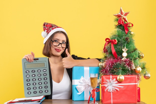 Femme charmante souriante en costume avec chapeau de père noël montrant la calculatrice faisant le geste ok dans le bureau sur jaune isolé