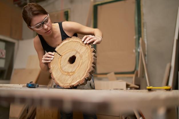 Femme charpentier dans des verres avec ruban à mesurer et scie arbre coupé dans ses mains en atelier