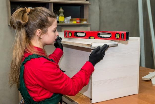 Femme charpentier mesure planche de bois en atelier