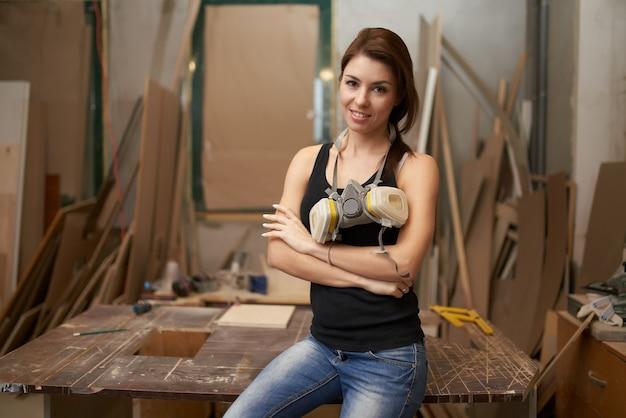 Femme charpentier avec respirateur assis sur un établi en atelier