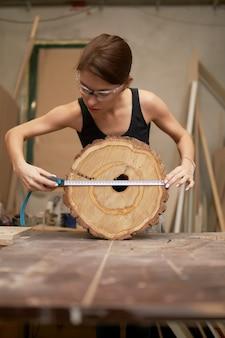 Femme charpentier avec ruban à mesurer et scie arbre coupé dans ses mains en atelier