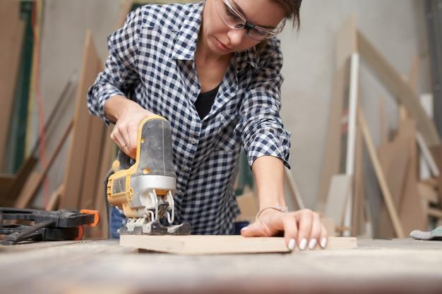 Femme charpentier travaillant avec une scie à chantourner en atelier.