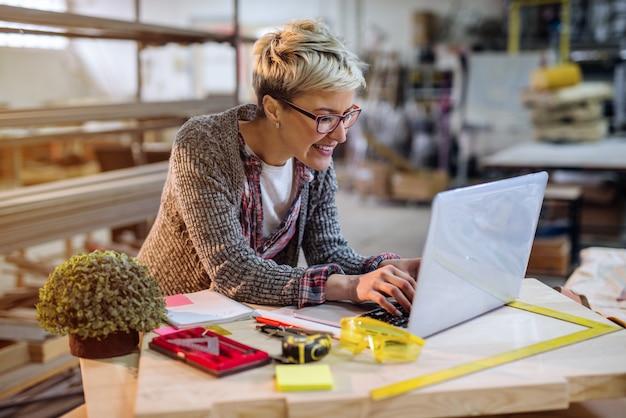 Femme charpentière à l'aide d'un ordinateur portable pour les calculs en se tenant debout dans l'atelier