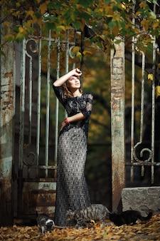 Femme avec des chats et une clôture de fer rouillé