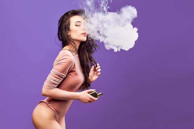 Femme chaude en body debout et vaping sur le mur violet.