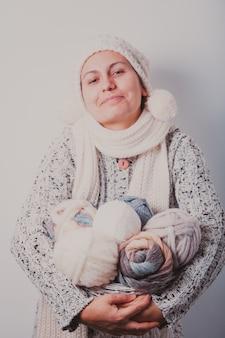 Femme chaudement vêtue tenant un panier de pelotes de laine