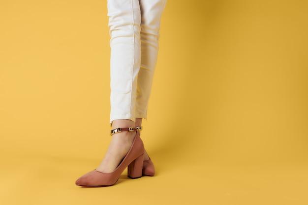 Femme en chaussures posant glamour fond jaune fashion