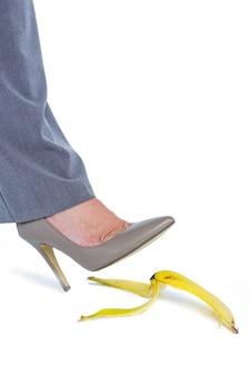 Femme avec des chaussures à talons marchant sur la banane