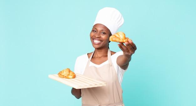 Femme de chef adulte afro-américaine noire tenant un plateau de croissants