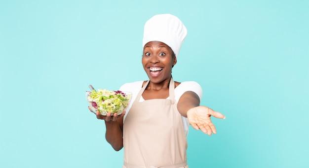 Femme de chef adulte afro-américaine noire tenant une salade