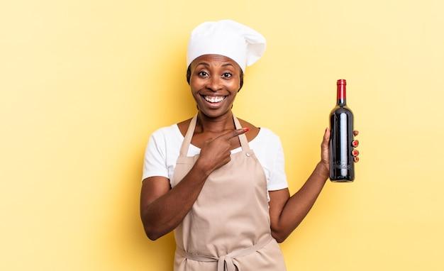 Femme chef afro noire à l'air excitée et surprise pointant sur le côté et vers le haut pour copier l'espace. concept de bouteille de vin