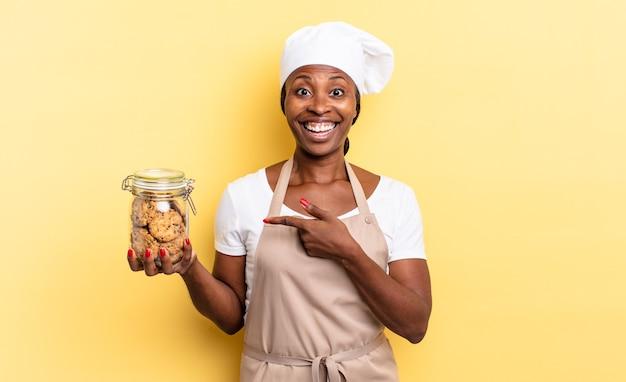 Femme chef afro noire à l'air excitée et surprise pointant sur le côté et vers le haut pour copier l'espace. notion de cookies
