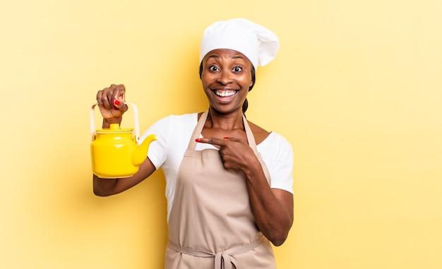 Femme chef afro noire à l'air excitée et surprise pointant sur le côté et vers le haut pour copier l'espace. notion de théière